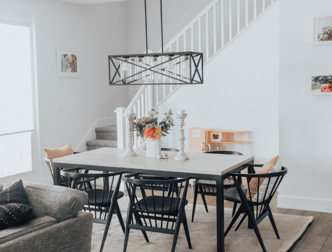 a bohemian modern inspired dining room with white and black accents, beautiful florals and pops of color, table room and board, light kichler