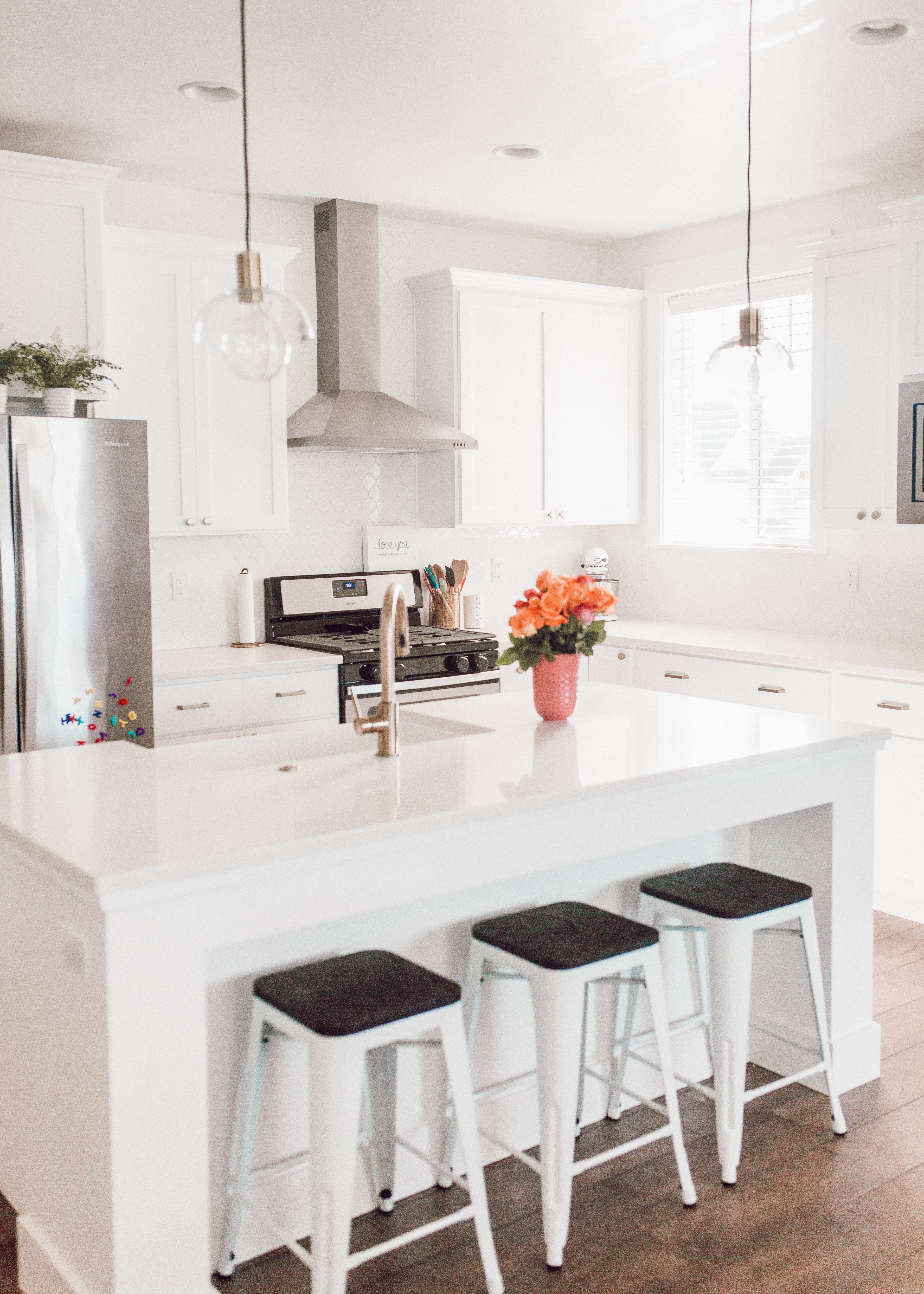 bohemian inspired modern white kitchen with lantern pattern backsplash and gold accents for a clean modern look that's affordable