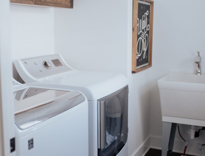 small, modern laundry room with clean finishes white walls, good storage, a sink and organization on a budget