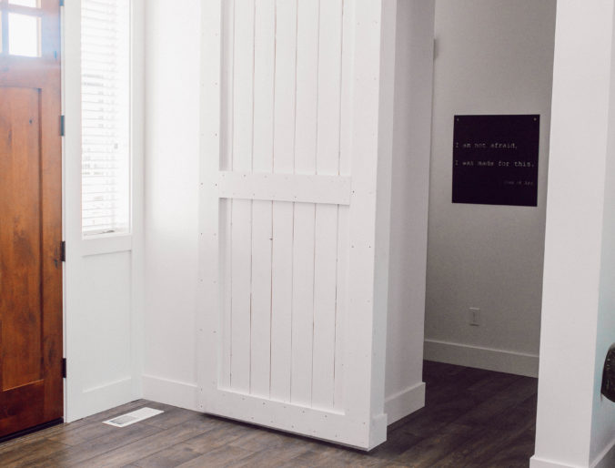 white barn door easily painted for an entry way to break up rooms, affordable black hardware with a bohemian look in the small entry way