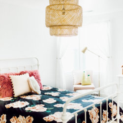 bohemian vibes, pink and white toddler girl's bedroom with metal white bed and bright accents modern farmhouse barn door