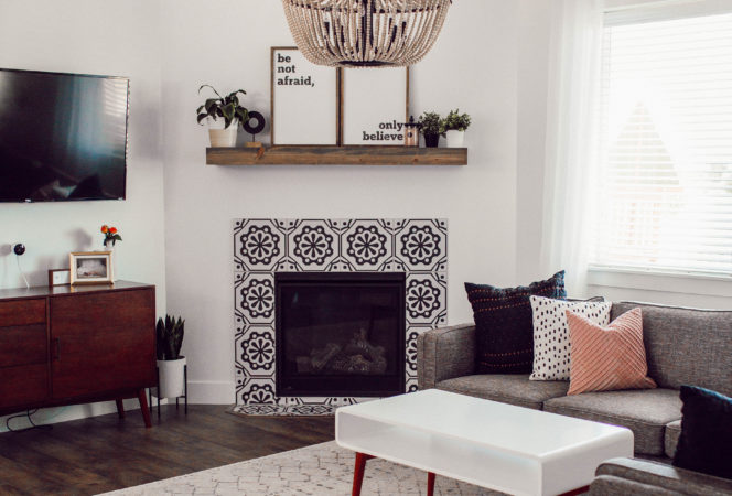 modern bohemian living room with clean white simple accents and pops of wood with a beaded chandelier and lots of greenery