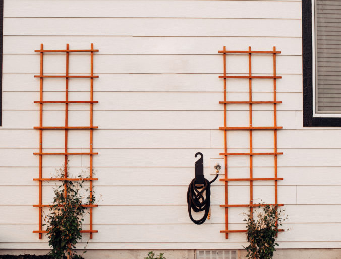diy trellis with vines on the back of a white house, wood trellis and an easy outdoor DIY project