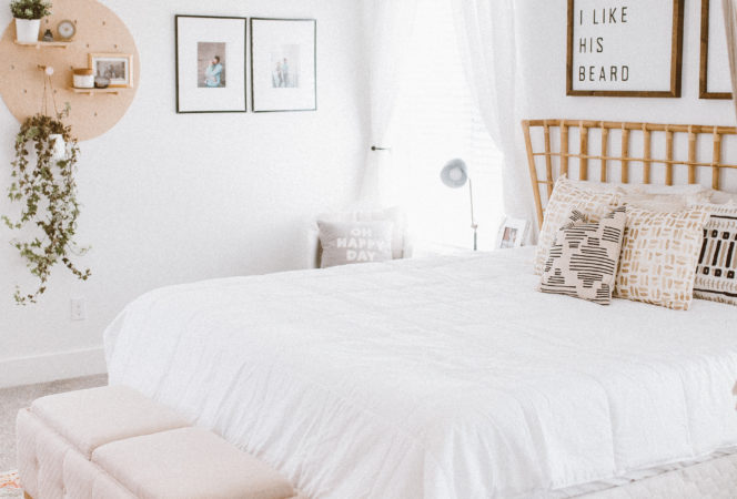 bohemian inspired white simple bedroom with accents of mid century modern, fun plants and lots of bright lighting. Complete with a hammock swing, barn door and pictures above the bed