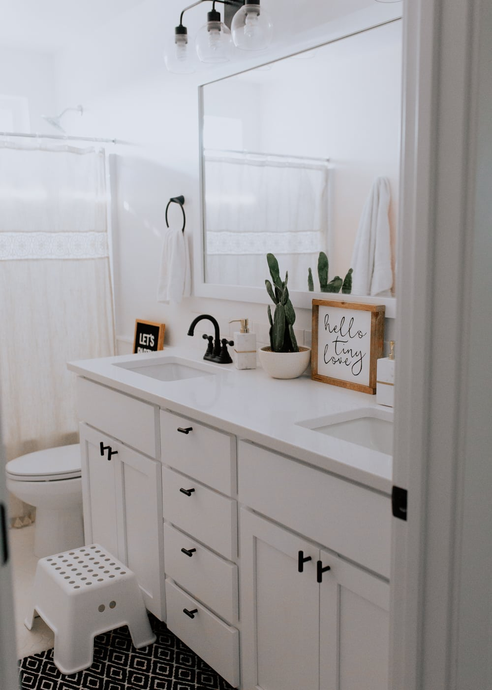 modern white bohemian kids bathroom with black accents and white hexagon tile and quartz counter tops