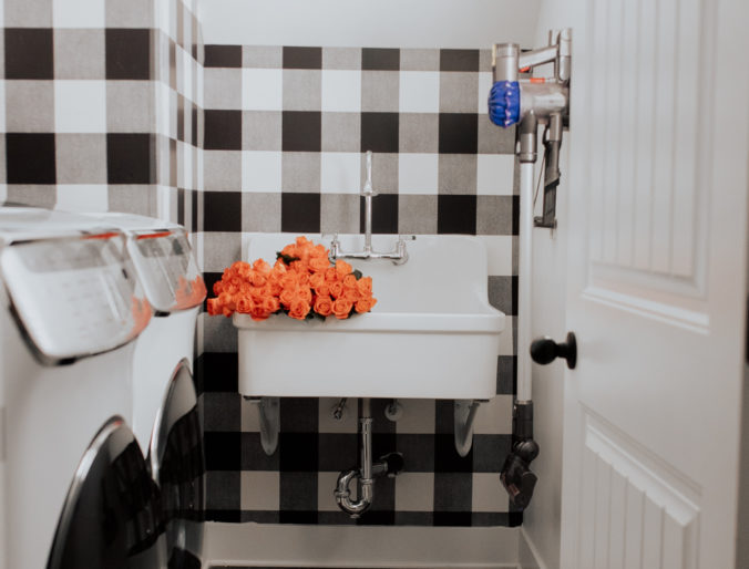 laundry room with black and white finishes, stainless steel, a farmhouse sink and a small area with lots of storage and organization - farmhouse, modern, boho inspired laundry room